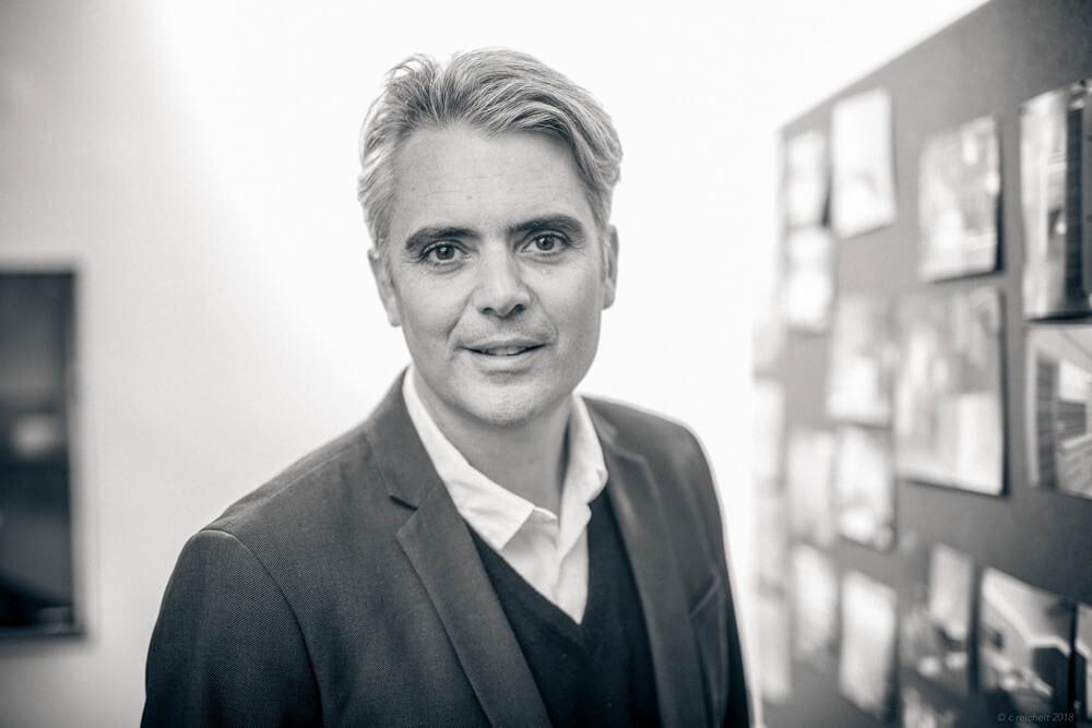Peter Döllmann in his office, facing camera, monocrome