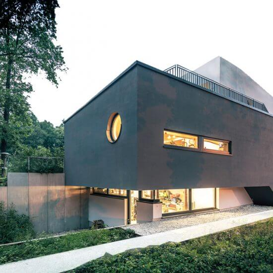 Ein modernes Einfamilienhaus - dunkle Fassade, schöner Garten